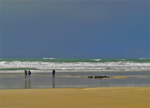 Picture of a beach with a wreck and three walkers under dark skies