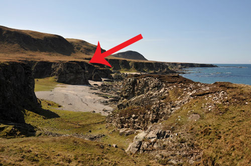Picture of a coast with steep cliffs and raised beaches, an arrow pointing to a location