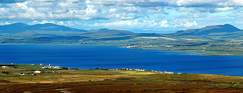 Picture of a view from a hill over a sea loch with two villages on the shore