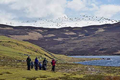 Picture of a group of walkers next to a loch